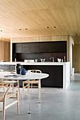 Esstisch mit Designerstühle vor offener Küche im Architektenhaus