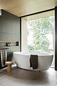 Floating, free-standing bathtub next to glass wall