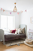 Old bed in vintage-style child's bedroom in muted shades