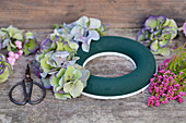 Ingredients for the autumn wreath: moist ring, hydrangea blossoms, topferika, snowberries and scissors