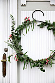Wintry wreath of eucalyptus and snowberries on door