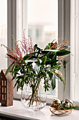 Wintry bouquet of leaves and grasses in glass vase on windowsill