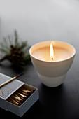 DIY-Teelicht, brennend und Steichhölzer