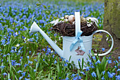 Easter basket made of twigs on a watering can between alpine squill