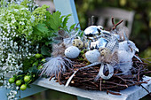 Easter nest of birch twigs with feathers, Easter eggs and Easter bunny