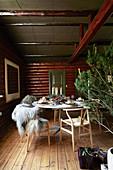 Festlich gedeckter Tisch mit Kerzen in einer Hütte