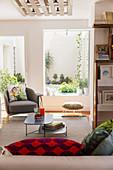 Grauer Sessel mit Kissen, Hocker und Couchtisch vor Fenster im Wohnzimmer