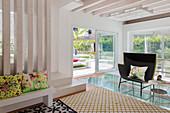 Designersessel und Beistelltisch auf Glasboden vor Terrassentür