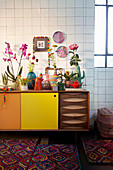 Various vases, cut flowers and houseplants on retro sideboard