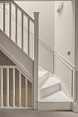 White staircase with white wooden banister and white wainscoting