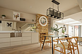 Brick fireplace and glass dining table in open-plan split-level kitchen