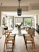 Glass dining table in raised dining area of open-plan interior
