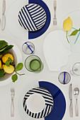 Gedeckter Tisch mit blau-weißem Geschirr dekoriert mit Zitronen