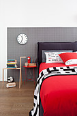 Red blanket on box spring bed with black headboard against grey checked wall