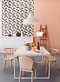 Pastel-pink wall, wallpaper with graphic pattern and tiled dado in dining room