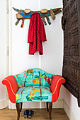 Antique armchair with brightly coloured upholstery next to African, carved, wooden doors decorating wall