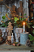 Christmas roses with branches of witch hazel, wooden decorative trees, Pinecones, and a candle