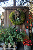 Christmas decoration with moss wreath, box with twigs and rose hips