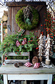 Christmas decoration with a moss wreath, box with branches, wooden trees and rose hips