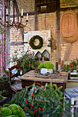 Moss wreath, conifer branches and rose hips in autumnal seating area in barn