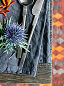 Thistle and cutlery on blue-grey linen napkin