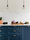 Vegetables on blue kitchen counter with marble worktop