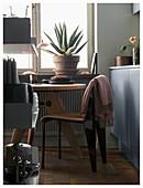 Düstere Wohnküche mit rundem Tisch vorm Fenster