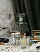 Perfume, jewellery box and pearl necklace on dressing table