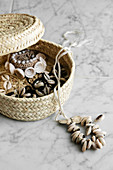 Jewellery made from shells in raffia basket on marble tile