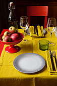 Bowl of apples on table set with yellow cloth