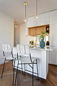 Barstools at island counter in small, white, open-plan kitchen