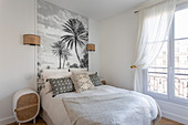 Bed against panel with palm-tree motif in classic bedroom