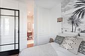 Concealed bathroom door in panelled bedroom wall