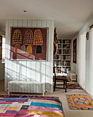 Ethnic picture and colourful accessories in wood-clad bedroom