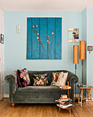 Grey velvet sofa with floral scatter cushions below blue artwork on pale blue wall