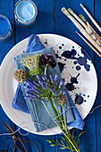 Agapanthus, scabious and blue napkin on speckled plate