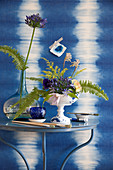 Arrangement of agapanthus and ferns in front of wall with blue ikat pattern