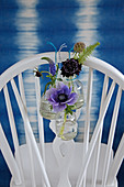 Anemone, veronica, scabious and fern in bottles hung from chairback