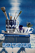 Paintbrushes and flower in cups on stack of blue books