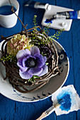 Carnation, anemone and scabious in nest of twigs