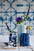 Anemone, veronica and drumstick flowers in blue vessels