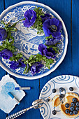 Wreath of anemones on blue plate, blueberries and artists' pastels