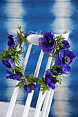 Wreath of anemones hung on backrest of white spoke-back chair in front of blue wall