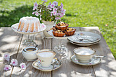 Table set for afternoon coffee with vintage-style crockery and DIY cake stands