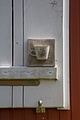 Candle lantern made from teacup embedded in concrete on window shutter