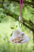 Bird feeder made from old teacup and saucer hung from bent spoon