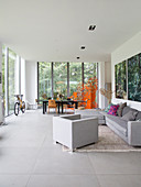 Grey sofa set and dining table in open-plan interior with glass walls