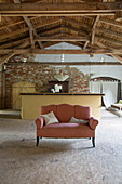 Sofa in front of counter in old barn with chipboard panels on floor