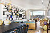 Black-painted dining table and shelves in open-plan interior with balcony