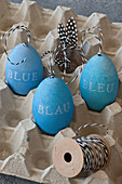 Blue Easter eggs decorated with lettering reading 'BLUE' in 3 languages